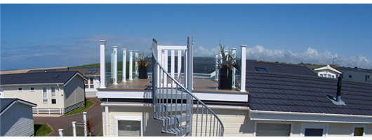 Clear glass frameless panels with white posts and coconut brown decking and spiral staircase