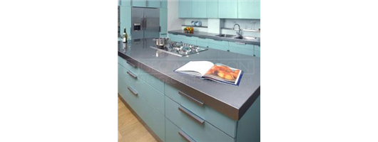 Domestic kitchen with stainless steel island top with cut out for hob and deep edge profile