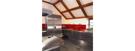 Domestic kitchen with cabinets, worktops, sinks and panelling in stainless steel