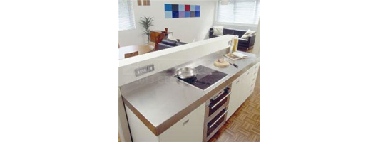 Stainless steel worktop with cut out for hob, deep edge profiles and integrated back upstand