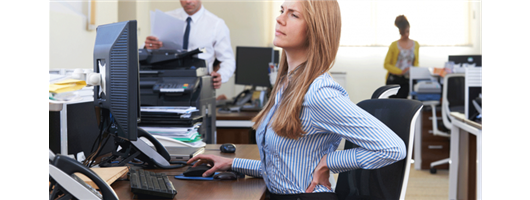 Woman Working At Desk Suffering From Backache