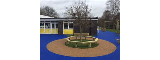 Tree seat in school playground with safe play surface surround